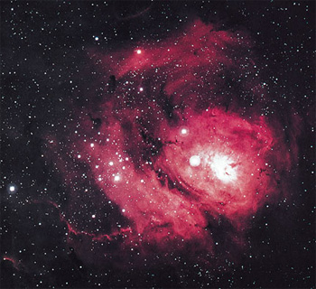 Figure 2: The Lagoon nebula is a cloud of gas and dust, about 60 light years in diameter. It is excited by the ultraviolet radiation of the hot stars that have recently formed within its bulk. (Horizons, Exploring the Universe, Seeds, plate 9, from Association of Universities for Research in Astronomy, Inc.)